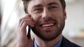 Smiling business man speaking phone emotionally at home. Guy calling cellphone.