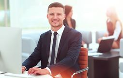 Smiling business man standing with his collegues in background a Royalty Free Stock Photo