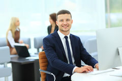 Smiling business man standing with his collegues in background a Royalty Free Stock Images