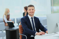 Smiling business man standing with his collegues in background a Royalty Free Stock Photos