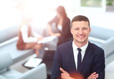 Smiling business man standing with his collegues in background a Stock Photography