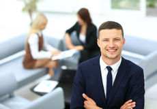 Smiling business man standing with his collegues in background a Royalty Free Stock Photography