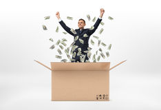 Smiling business man standing in open big cardboard mail box and dollar bills are falling around him, isolated on the