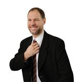 Smiling business man straightens his tie Royalty Free Stock Photos
