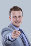 Smiling business man in a suit pointing with his finger Royalty Free Stock Photo