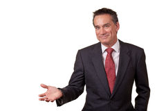Smiling Business Man in Suit Showing Copy Space. Attractive Smiling Middle Age Business Man Gesturing with Open Hand Royalty Free Stock Image