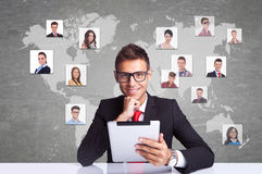 Smiling business man with tablet pad networking. Collage with a smiling business men with tablet pad  against technology background, communicating with entire Royalty Free Stock Photo