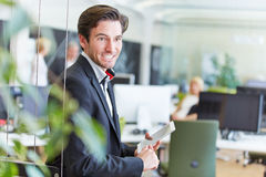 Smiling business man with tablet PC in office Royalty Free Stock Photos