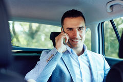 Smiling business man talking on cell phone in the car Stock Photography