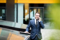Smiling business man talking smartphone near office building royalty free stock photography
