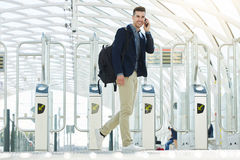 Smiling business man by turnstile on phone call Stock Images