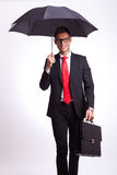 Smiling business man under an umbrella walking Royalty Free Stock Photos