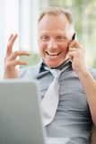 Smiling business man using cellphone and laptop Royalty Free Stock Photography