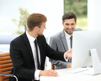 Smiling business men showing something on computer as colleague Royalty Free Stock Image