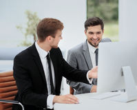 Smiling business men showing something on computer as colleague Stock Photo