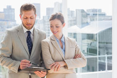 Smiling business partners going over document on clipboard Stock Images