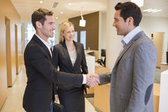 Smiling Business partners shaking hands in hall, lobby royalty free stock photos