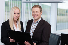 Smiling business partners using a laptop stock photography