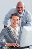 Smiling business partners working at a computer Stock Photo