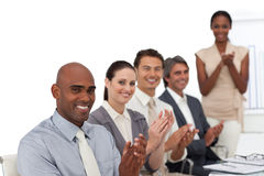 Smiling business people applauding. Multi-ethnic business people applauding after a presentation in the office Stock Images