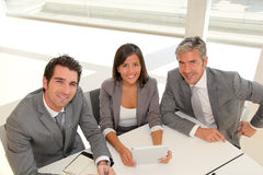 Smiling business people around meeting tablet stock images
