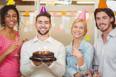 Smiling business people with birthday cake. Portrait of smiling business people with birthday cake in creative office Royalty Free Stock Photography