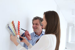 Smiling business people choosing color samples against wall in office royalty free stock photography