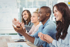 Smiling business people clapping at desk Stock Photos