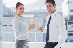 Smiling business people clinking their flutes of champagne Stock Photos