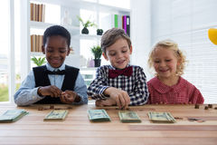 Smiling business people counting money while standing at table in office. Smiling business people counting money while standing at table in creative office Royalty Free Stock Photos