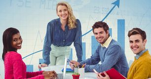 Smiling business people at desk against graph Stock Photo