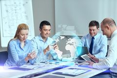 Smiling business people with gadgets in office. Business, people, cooperation and technology concept - smiling business team with gadgets and globe hologram royalty free stock photo