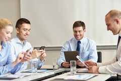 Smiling business people with gadgets in office Royalty Free Stock Photos