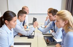Smiling business people having conflict in office Stock Photo