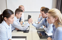 Smiling business people having conflict in office Stock Photos