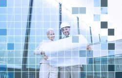 Smiling business people in helmets with blueprint Royalty Free Stock Photo