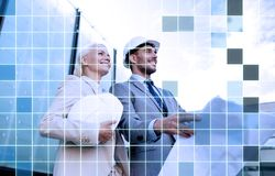 Smiling business people in helmets with blueprint Royalty Free Stock Photos