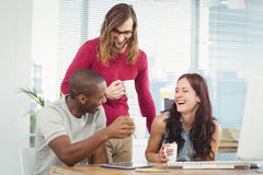 Smiling business people holding coffee cups at computer desk Royalty Free Stock Photography