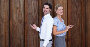Smiling business people holding smart phone while standing back to back against wooden wall Royalty Free Stock Photos