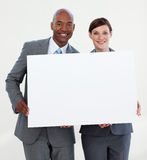 Smiling business people holding white card Stock Photo