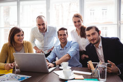 Smiling business people with laptop in meeting room Royalty Free Stock Image