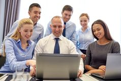 Smiling business people with laptop in office Royalty Free Stock Photo
