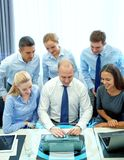 Smiling business people with laptop in office Stock Photos