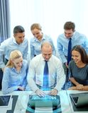 Smiling business people with laptop in office Royalty Free Stock Photos