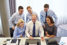 Smiling business people with laptop in office Royalty Free Stock Images
