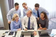 Smiling business people with laptop in office Stock Photo
