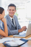 Smiling business people look at each other Royalty Free Stock Images