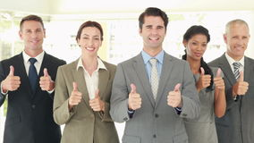 Smiling business people looking at camera gesturing thumbs up stock video