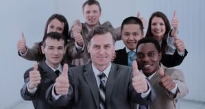 Happy colleagues  showing thumbs up in their office. Stock Images
