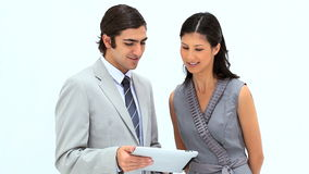 Smiling business people looking at a tablet computer. Against a white background stock footage